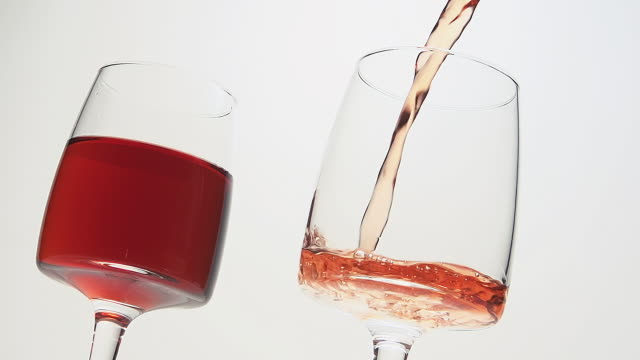 cu slo mo shot of pink wine being pour into glass against white background / calvados, normandy, france - two objects stock videos and b-roll footage