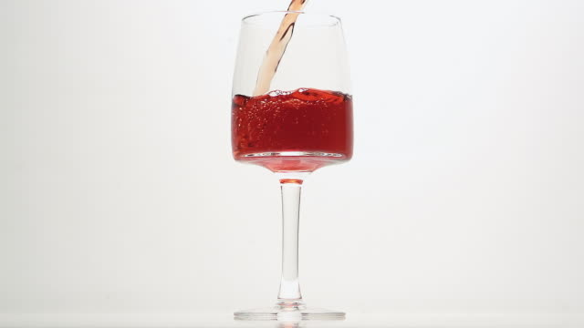cu slo mo shot of pink wine being pour into glass against white background / calvados, normandy, france - calvados stock videos and b-roll footage