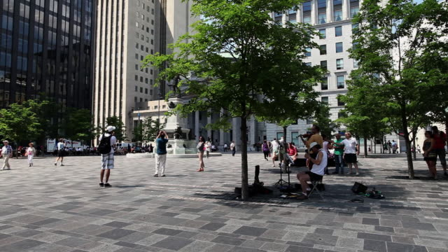 ms pan shot of place d'armes square at old montreal / montreal, quebec, canada - モントリオール旧市街点の映像素材/bロール
