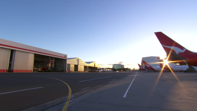 WS PAN Shot of Plane and hanger, into sun / Mascot, New South Wales, Australia