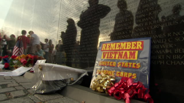 ms shot of plaque saying remember vietnam next to us marine hat left at vietnam veterans memorial wall / washington, district of columbia, united states - vietnam veterans memorial video stock e b–roll