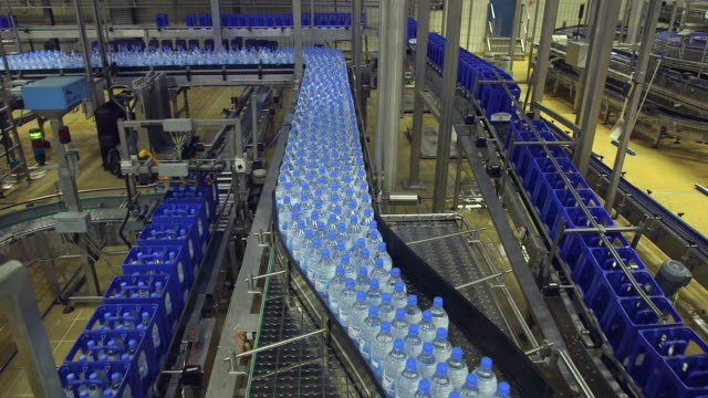ms shot of plastic bottle and carret moving in bottling plant at beverage industry / gerolstein, rhineland palatinate, germany  - attrezzatura industriale video stock e b–roll
