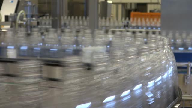 cu shot of plastic bottle moving in bottling plant at beverage industry / gerolstein, rhineland palatinate, germany  - water bottle stock videos & royalty-free footage
