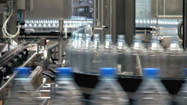 ms shot of plastic bottle moving in bottling plant at beverage industry / gerolstein, rhineland palatinate, germany  - bottiglia video stock e b–roll