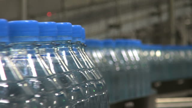 cu shot of plastic bottle moving in bottling plant at beverage industry / gerolstein, rhineland palatinate, germany  - bottiglia video stock e b–roll