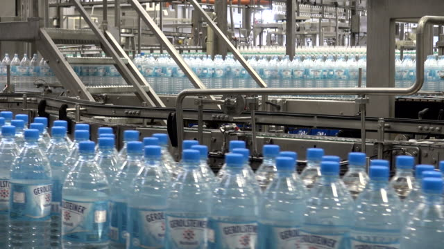 MS Shot of plastic bottle moving in bottling plant at beverage industry / Gerolstein, Rhineland Palatinate, Germany