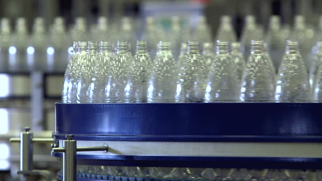 ms shot of plastic bottle moving in bottling plant at beverage industry / gerolstein, rhineland palatinate, germany  - flasche stock-videos und b-roll-filmmaterial