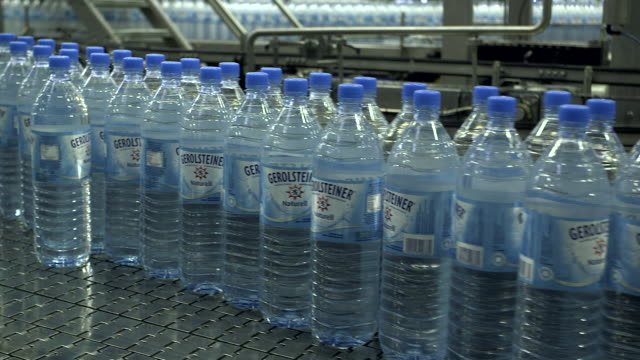 ms shot of plastic bottle moving in bottling plant at beverage industry / gerolstein, rhineland palatinate, germany  - water bottle stock videos and b-roll footage