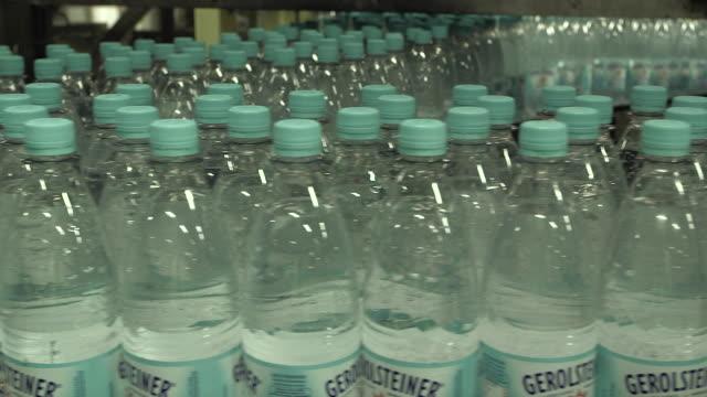 cu shot of plastic bottle moving in bottling plant at beverage industry / gerolstein, rhineland palatinate, germany  - bottling plant stock videos & royalty-free footage