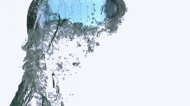 CU SLO MO Shot of Plastic Bottle of Water falling and Splashing against White Background / Calvados, Normandy, France