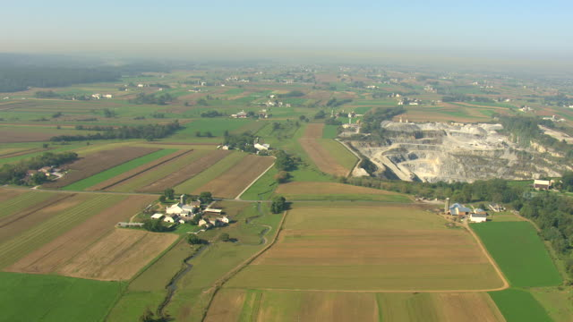 WS AERIAL Shot of plowed fields and quarry in Amish country / Pennsylvania, United States