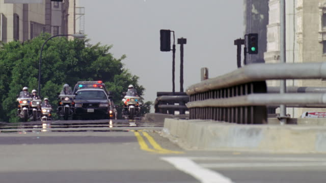 ws shot of police escorted limousine and suv motorcade through city - motorcade stock videos & royalty-free footage