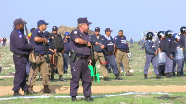 MS Shot of police in riot gear holding their weapons during protests in mitchells plain township / Cape Town, South Africa