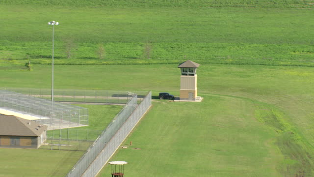 MS AERIAL TS Shot of police lookout tower to angola prisonlouisiana state penitentiary buildings / Angola, Louisiana, United States