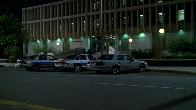 MS Shot of Police station with police cars parked out in front and people with police man moving in and out