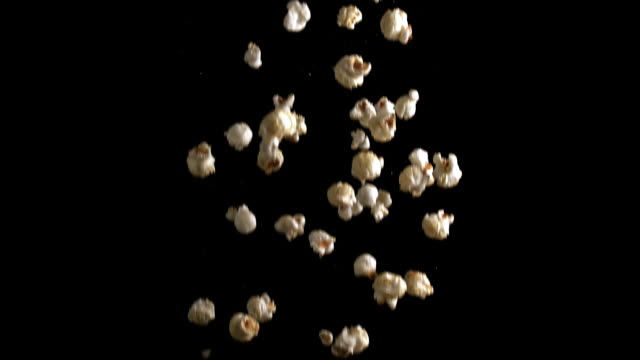 CU SLO MO Shot of Popcorn falling against black background / Calvados, Normandy, France
