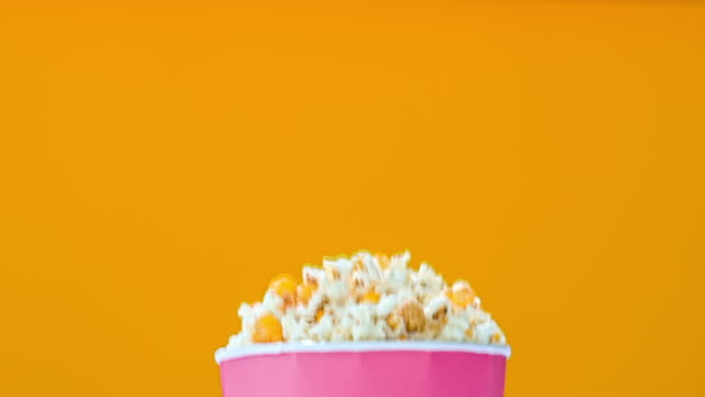 shot of popcorn falling out a box on yellow background - popcorn stock-videos und b-roll-filmmaterial