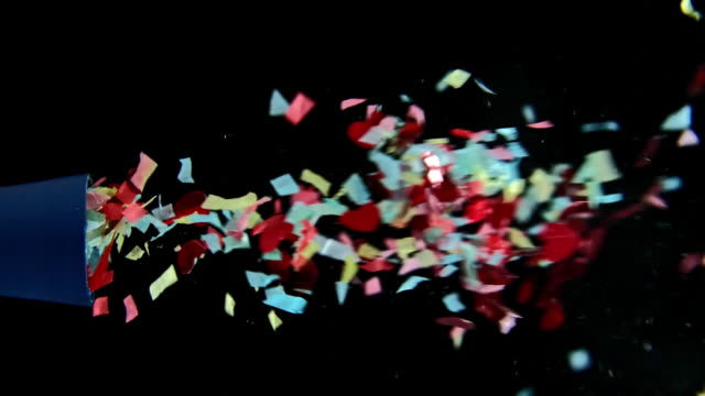 shot of popping party popper with colourful confetti on black background - confetti stock videos & royalty-free footage