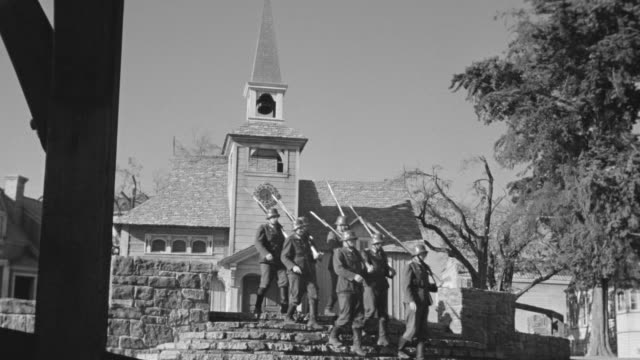 ws shot of porch through town to church and soldiers marching - marching stock videos and b-roll footage