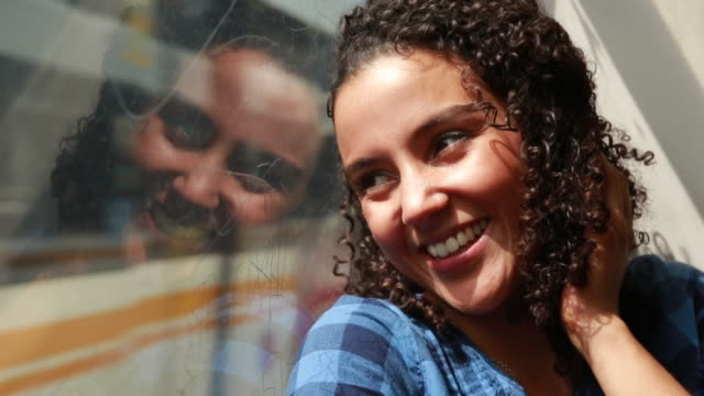 CU ZO SLO MO Shot of Portrait of Young woman smiling and looking out moving metro train window / Los Angeles, California, United States