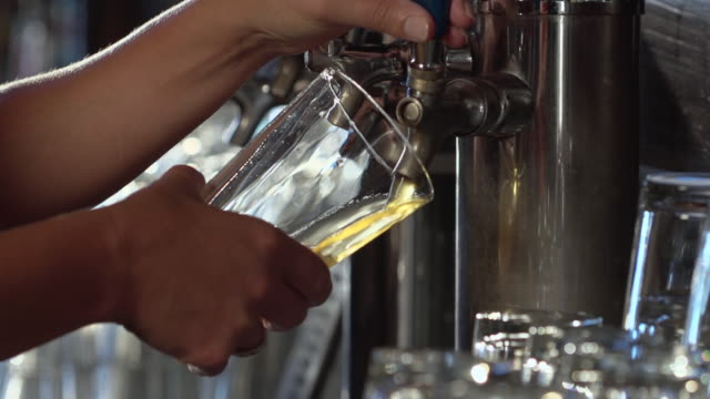 cu slo mo shot of pouring beer on tap into glass / seattle, washington, united states - zapfen stock-videos und b-roll-filmmaterial