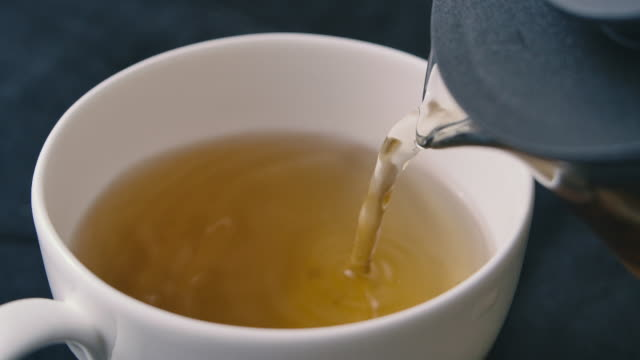 SLO MO Shot of Pouring Black Tea into Cup Fine dining afternoon tea