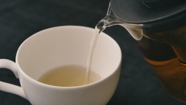 slo mo shot of pouring black tea into cup - black tea stock videos & royalty-free footage