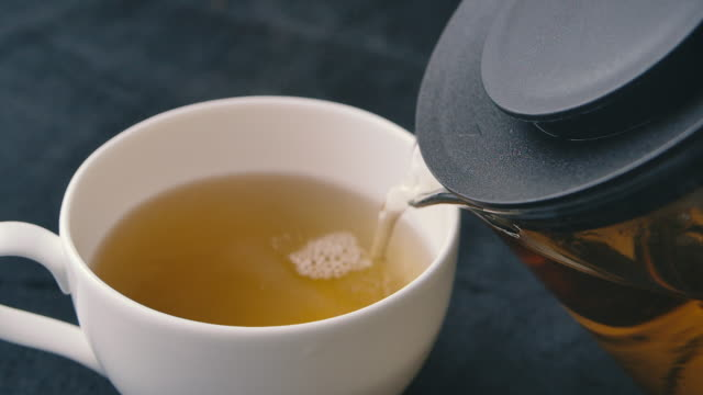 slo mo shot of pouring black tea into cup - tea cup stock videos & royalty-free footage