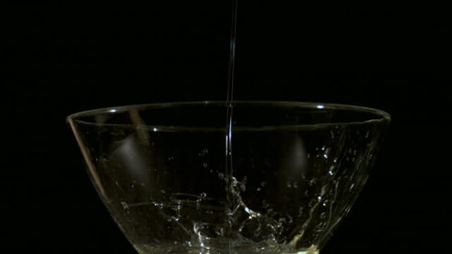 Shot of Pouring Cooking Oil in Glass Bowl