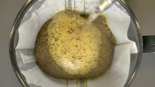 stockvideo's en b-roll-footage met shot of pouring hot water into dripper for making hand drip coffee - dranken