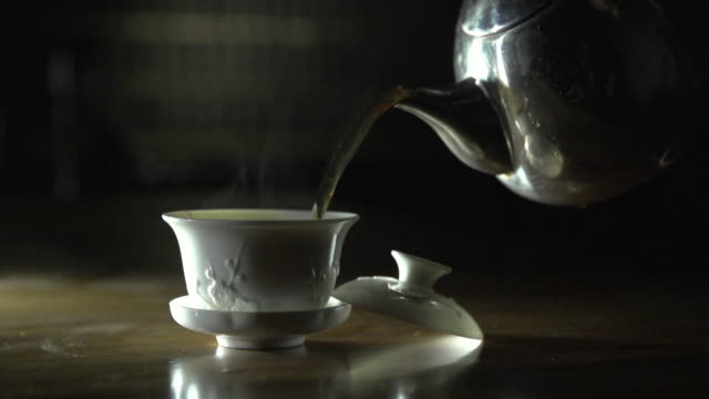 shot of pouring tea into a tea cup - tea cup stock videos & royalty-free footage