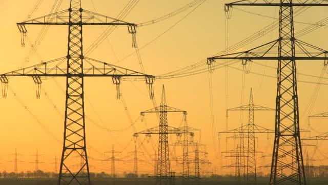 ws shot of power lines and towers at sunrise / niederaubem, north rhine westphalia, germany - power line点の映像素材/bロール