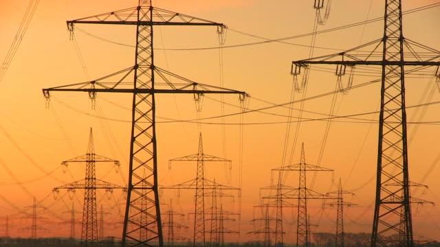 ws shot of power lines and towers with windmills at sunrise / niederaubem, north rhine westphalia, germany - power line点の映像素材/bロール