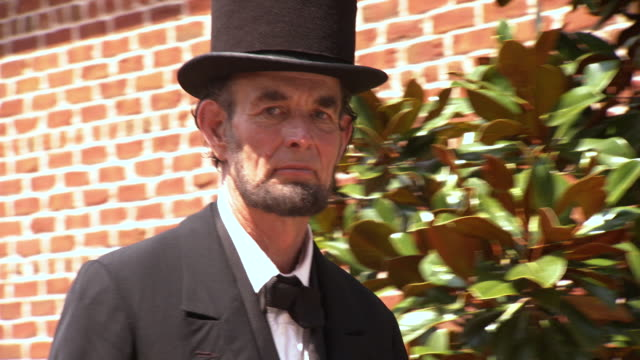 CU TS Shot of President Abraham Lincoln Abraham Lincoln tips his hat to African American woman and she looks back smiling / Clear Spring, Maryland, United States
