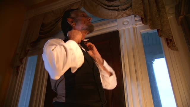 MS TU TD Shot of President Abraham Lincoln adjusting his ties and buttons up his cuffs / Clear Spring, Maryland, United States