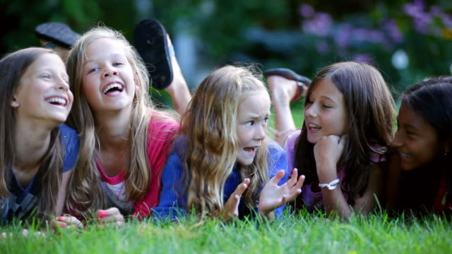 vidéos et rushes de ms pan shot of preteen girls gossiping on grass / manchester, vermont, united states - parler
