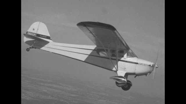 shot of preteen or teenaged boy in cockpit flying taylorcraft airplane / shot from another plane of plane flown by boy in flight / plane flown by boy... - プロペラ機点の映像素材/bロール