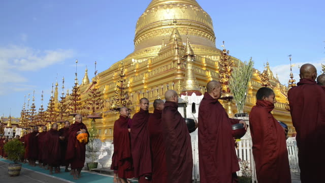 MS Shot of Procession of Buddhist monks at Full Moon Festival in front of golden Stupa of Shwezigon Pagoda / Bagan, Mandalay Division, Myanmar