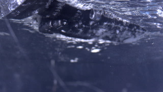 shot of professional video camera drowning into water - drowning stock videos and b-roll footage
