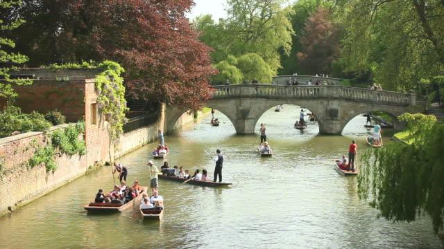 ms shot of punters on river cam by bridge behind kings college cambridge / cambridge, cambridgeshire, united kingdom - 史跡めぐり点の映像素材/bロール