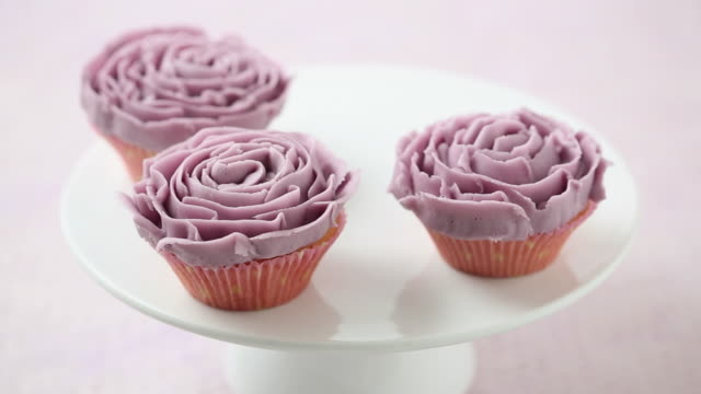 ms shot of purple iced cupcake placed on white dish in centre / london, united kingdom  - cupcake stock videos & royalty-free footage