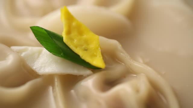 vídeos de stock, filmes e b-roll de ecu shot of putting garnish on manduguk(dumpling(wonton) soup) / seoul, south korea - bolinho de massa