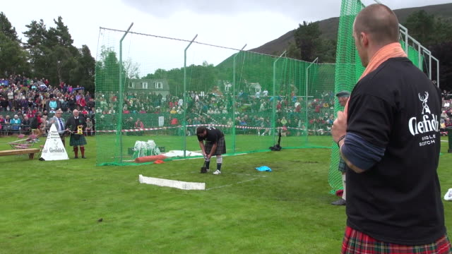 ms pan shot of putting stone at braemar royal highland games / braemar, aberdeenshire, scotland - highland games stock videos & royalty-free footage
