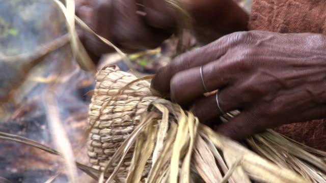 vídeos y material grabado en eventos de stock de cu shot of pygmy woman hands weaving hat out of palms / kigez, kabale, uganda - tejer