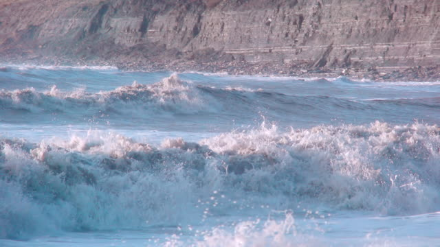 MS PAN SLO MO Shot of raging sea in front of cliffs of Jurassic Lower Lias at Monmouth Beach, Lyme Regis / Newcastle Emlyn, Ceredigion, United Kingdom