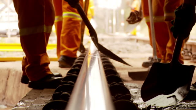 stockvideo's en b-roll-footage met cu r/f shot of rail road workers digging around train track / south africa - infaden