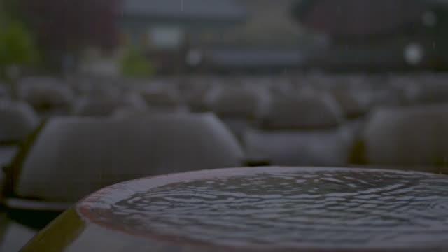 shot of rain falling on jang dok dae (korean earthenware jar for fermenting food) - 陶器点の映像素材/bロール