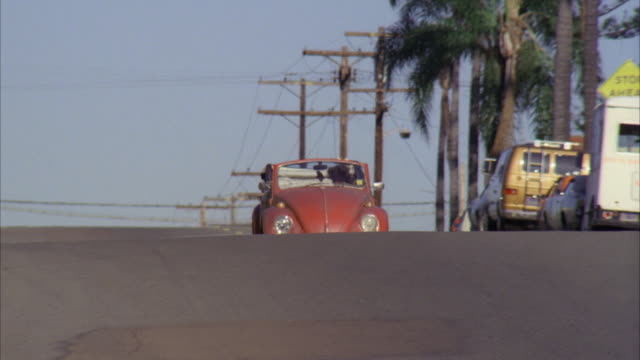 ms pan shot of red convertible volkswagen passing on san diego residential street - 1980 stock videos and b-roll footage