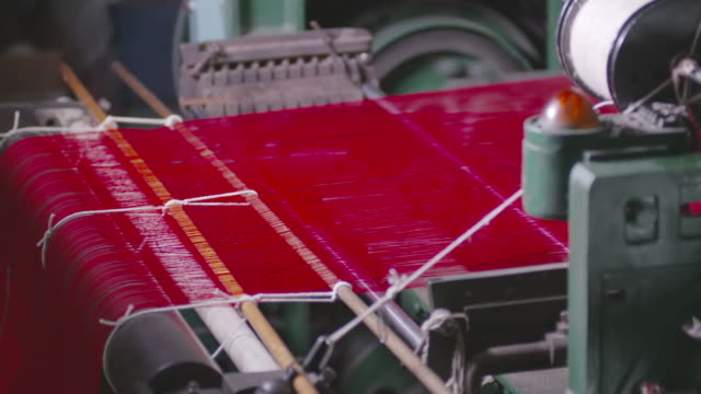 ms shot of red fabric being weaved in power loom / red lion, pennsylvania, united states  - loom stock videos & royalty-free footage