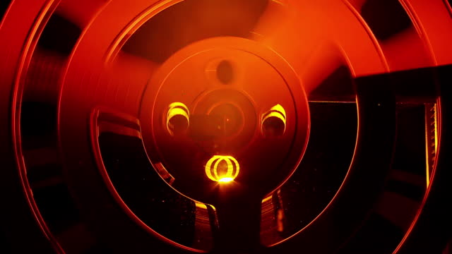 cu shot of red light falling on spinning reel / london, united kingdom  - film reel stock videos & royalty-free footage